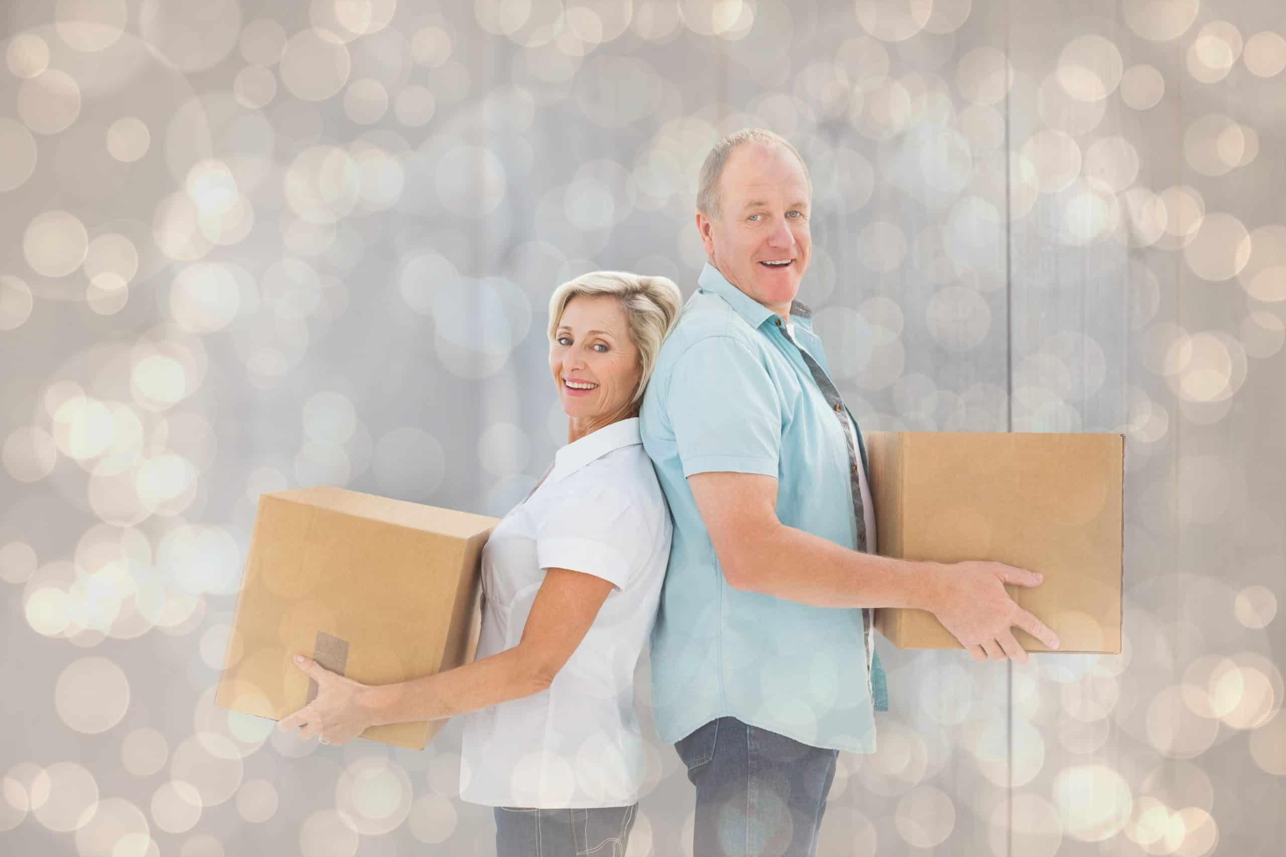 Declutter your home - Happy older couple holding moving boxes against light glowing dots design pattern