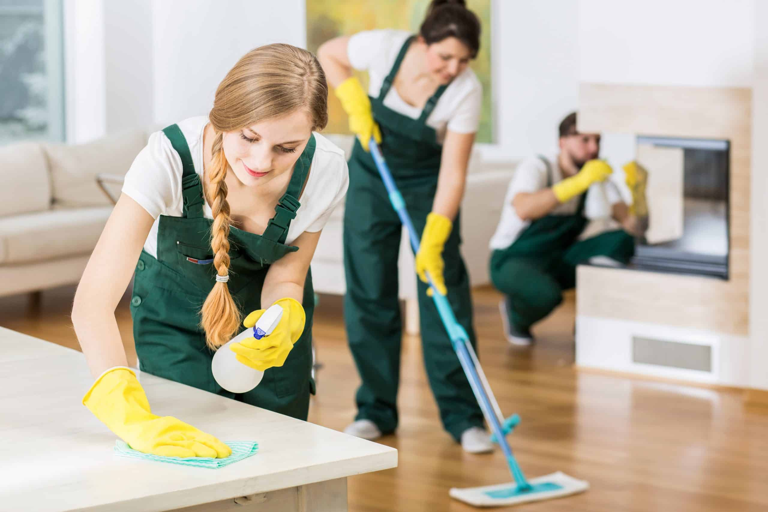 Spend time to save money - Team of 3 house cleaners in green overalls clean a living room