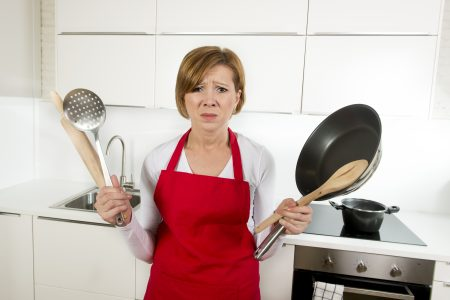 Unhappy woman in the kitchen with pots and utensils