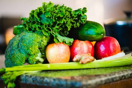 Eat healthy on a budget - pile of produce with lettuce, apples, celery, cucumber