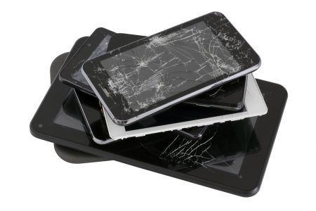 a stack of old cell phones, tablet, with cracked screens