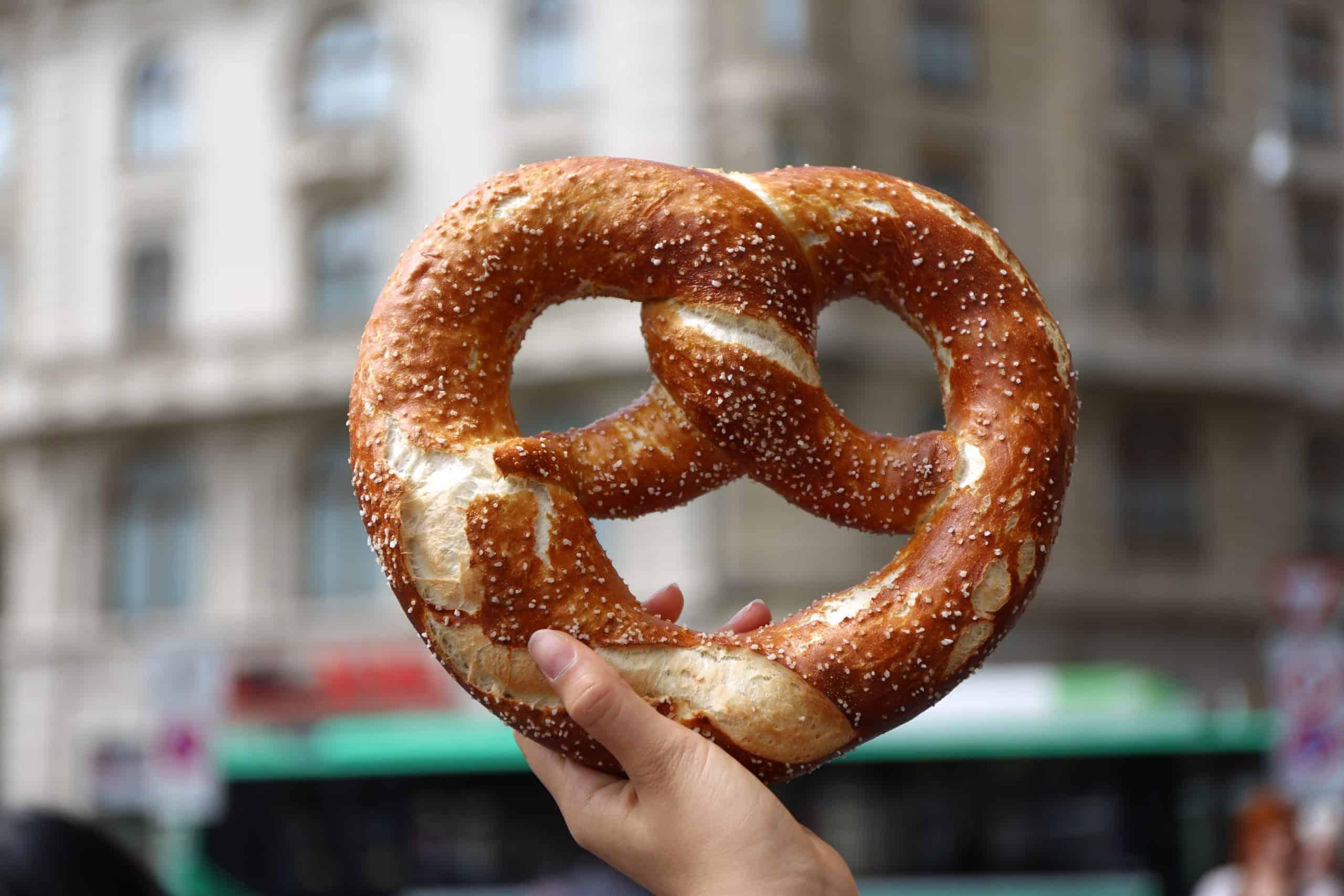 National Pretzel Day Deals - hand holding up a soft pretzel against an urban setting