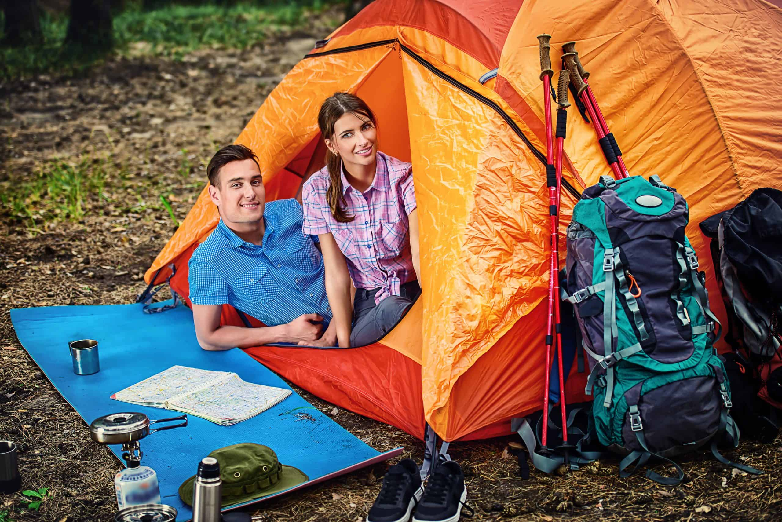 Used outdoor gear - Happy man-woman couple in an orange tent surrounding by backpacks and hiking poles