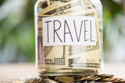 "Travel hacks - Jar with 100 dollar bills, labeled ""travel"""