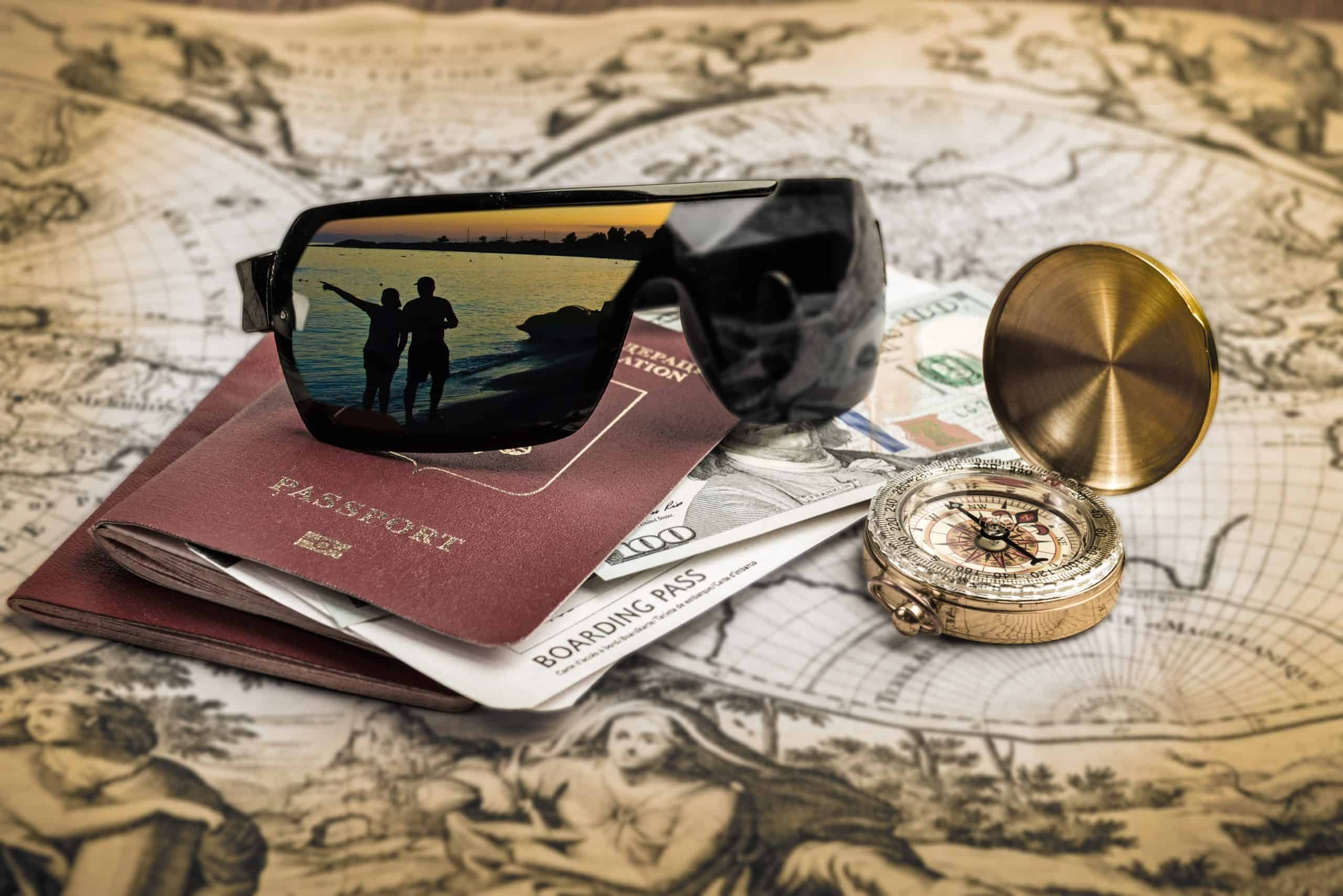 Travel hacks - Passport with sunglasses and compasses on old map