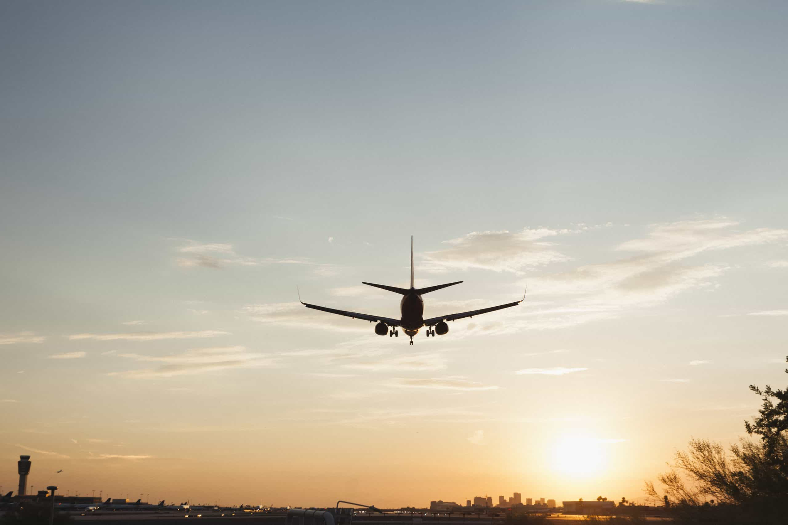 Travel hacks - Plane flying into Phoenix Sky Harbor Airport with sun setting in background