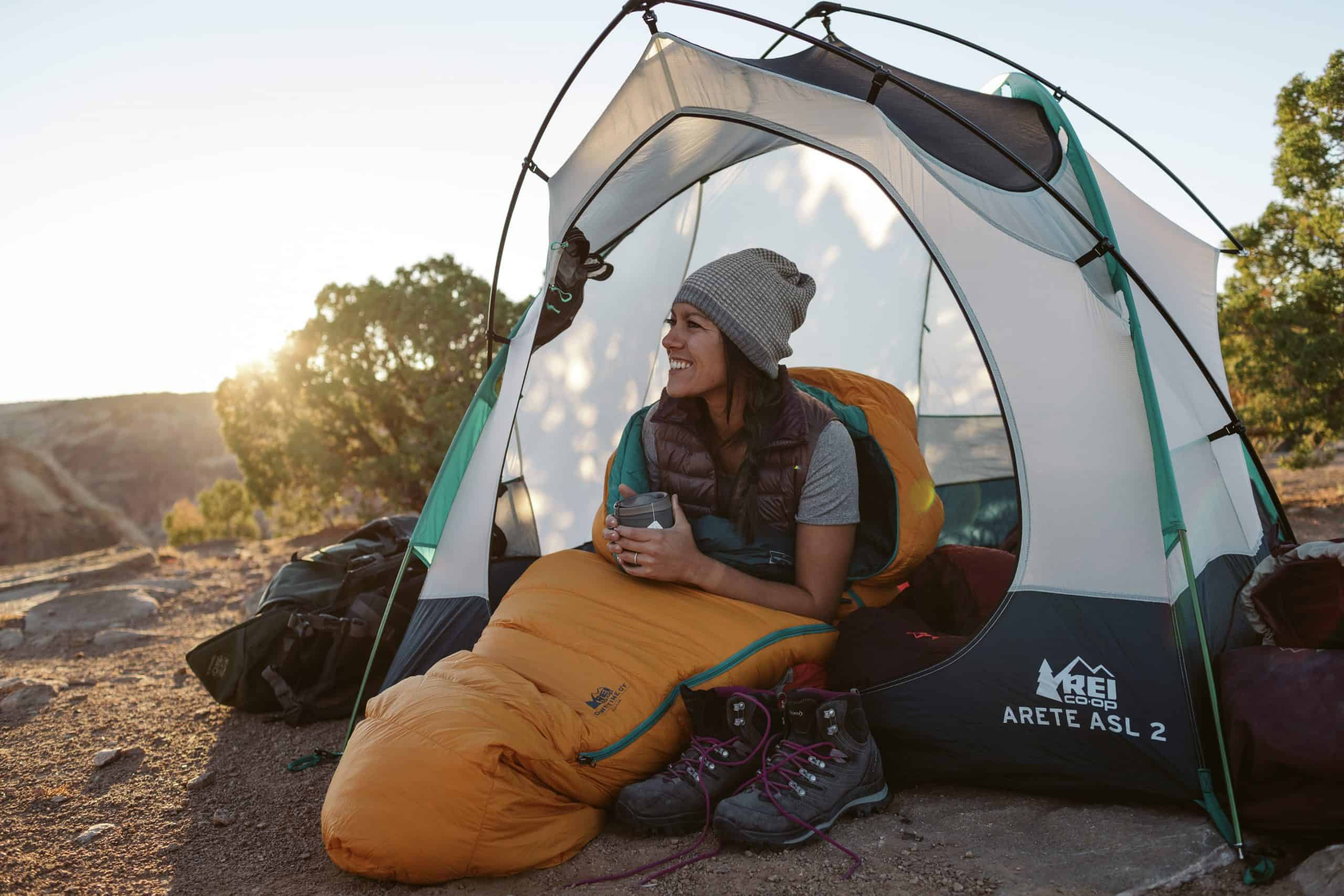 Used outdoor gear - Woman in sleeping bag sitting in doorway of tent with her rented REI gear