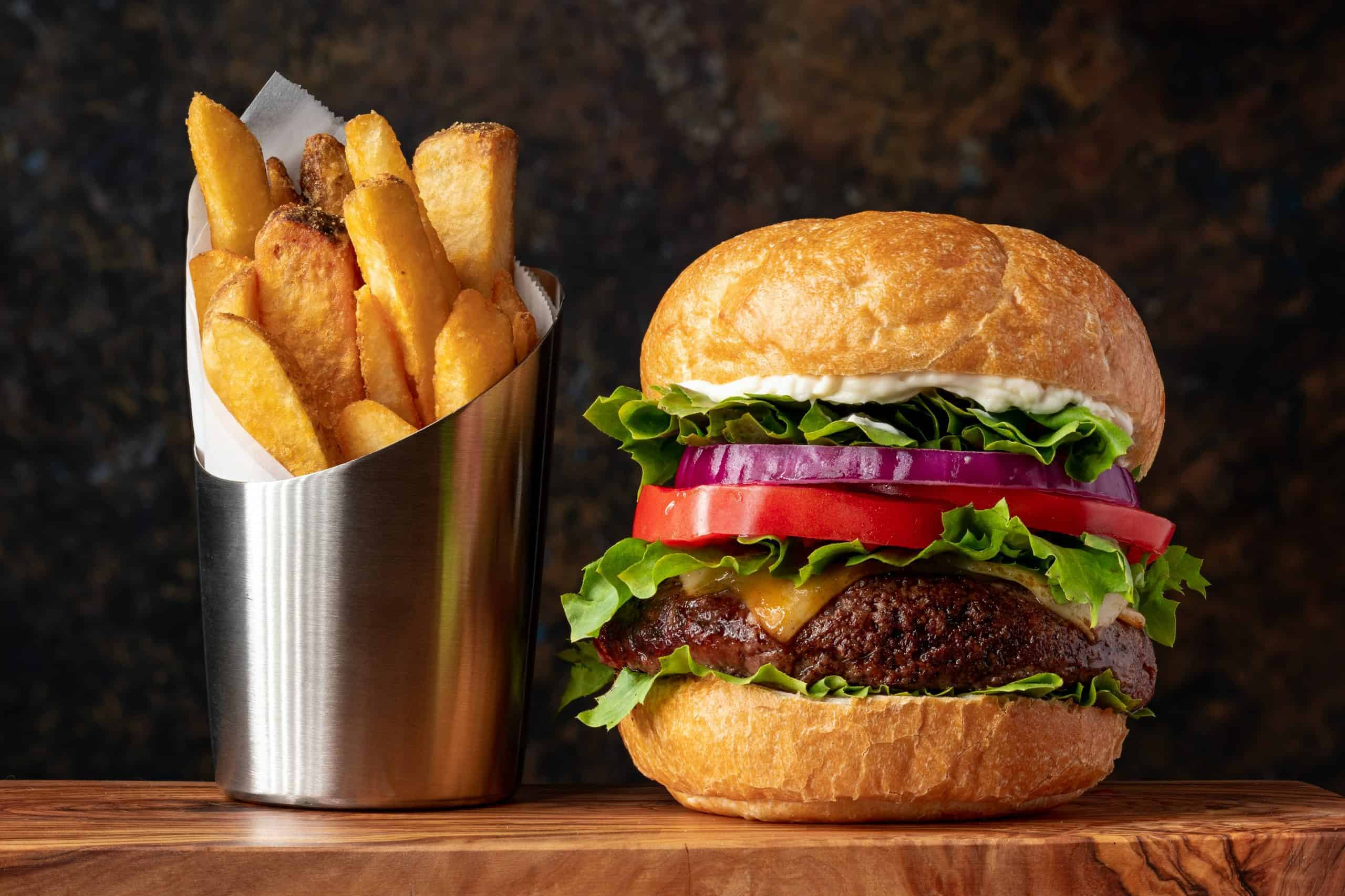 Hamburger day deals - Picture of cheeseburger with lettuce, tomato and red onion next to metal container of thick steak fries
