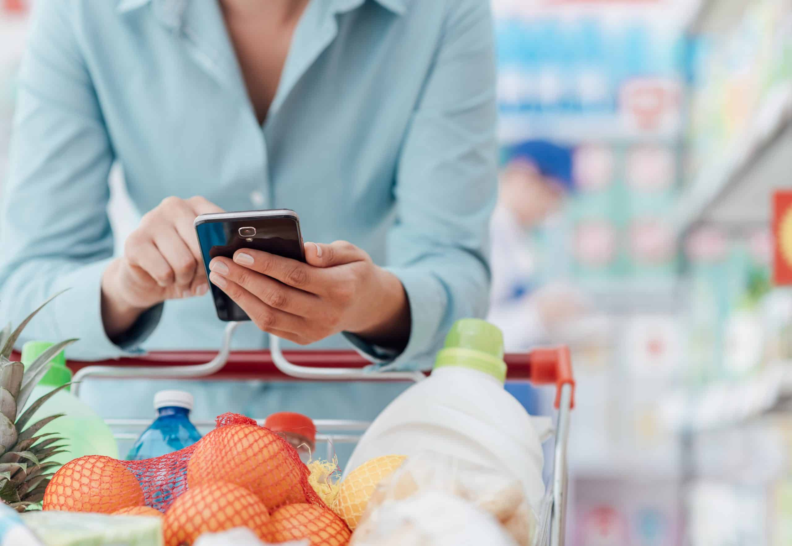 More frugal than your spouse - Woman in blue button-down shirt looking at phone app by her supermarket shopping cart