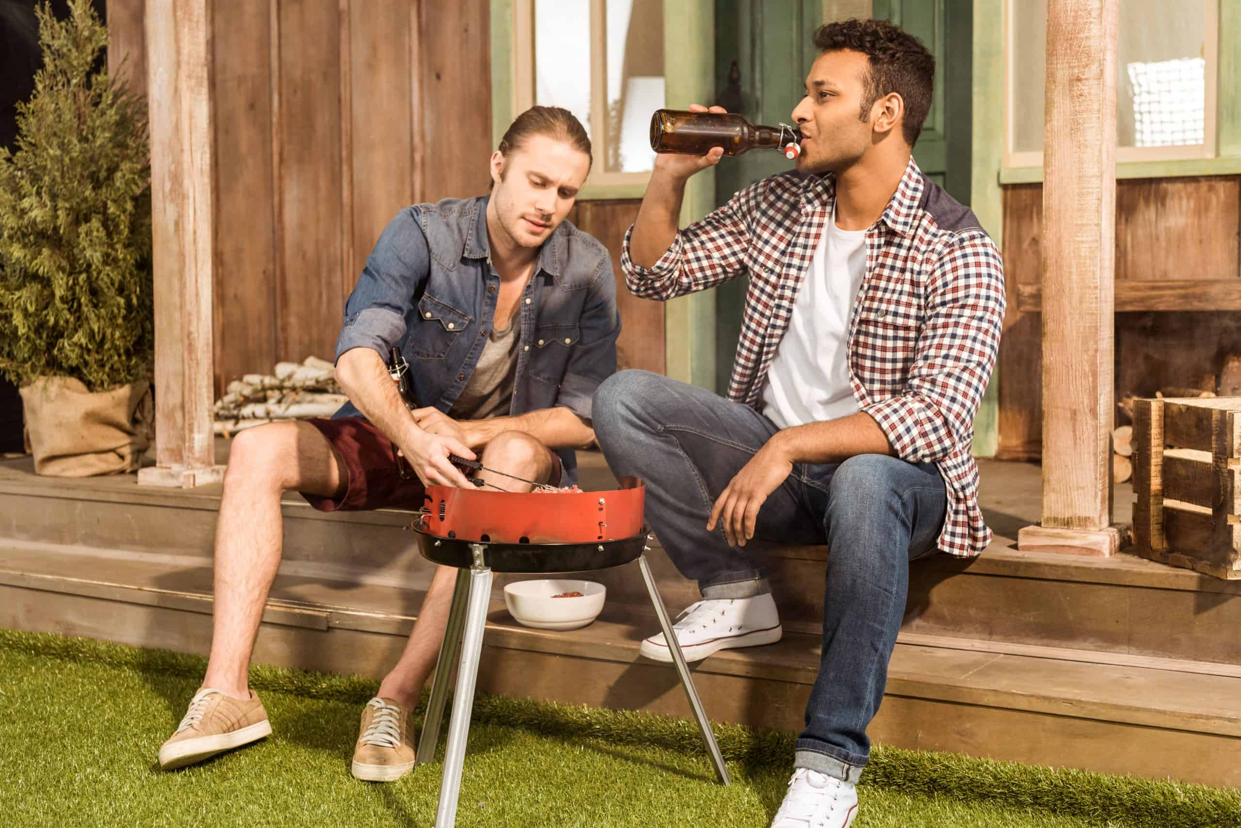 Barbecue safety tips - two men grilling and drinking beer