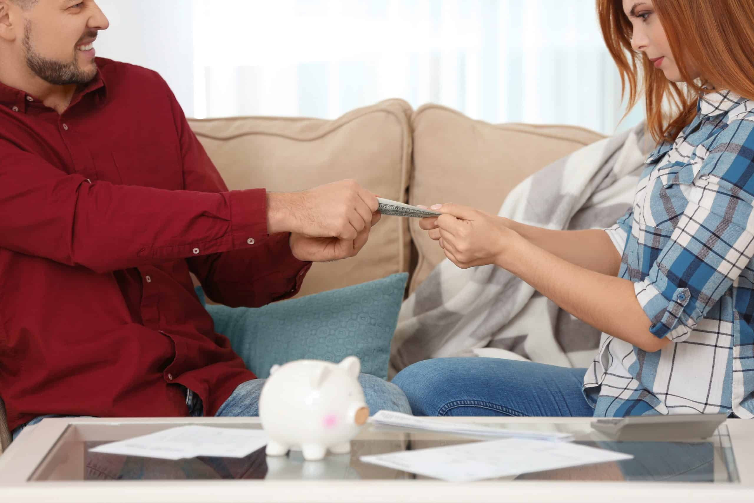 More frugal than your spouse - Couple fighting over dollar bill at home
