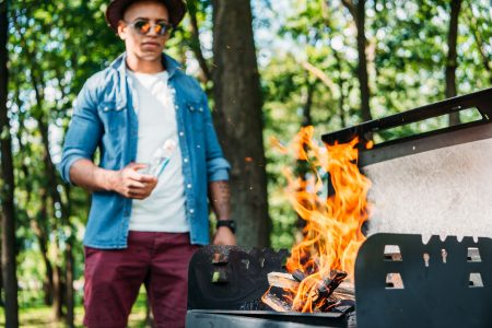 Barbecue safety tips - Man grilling in park with large flame