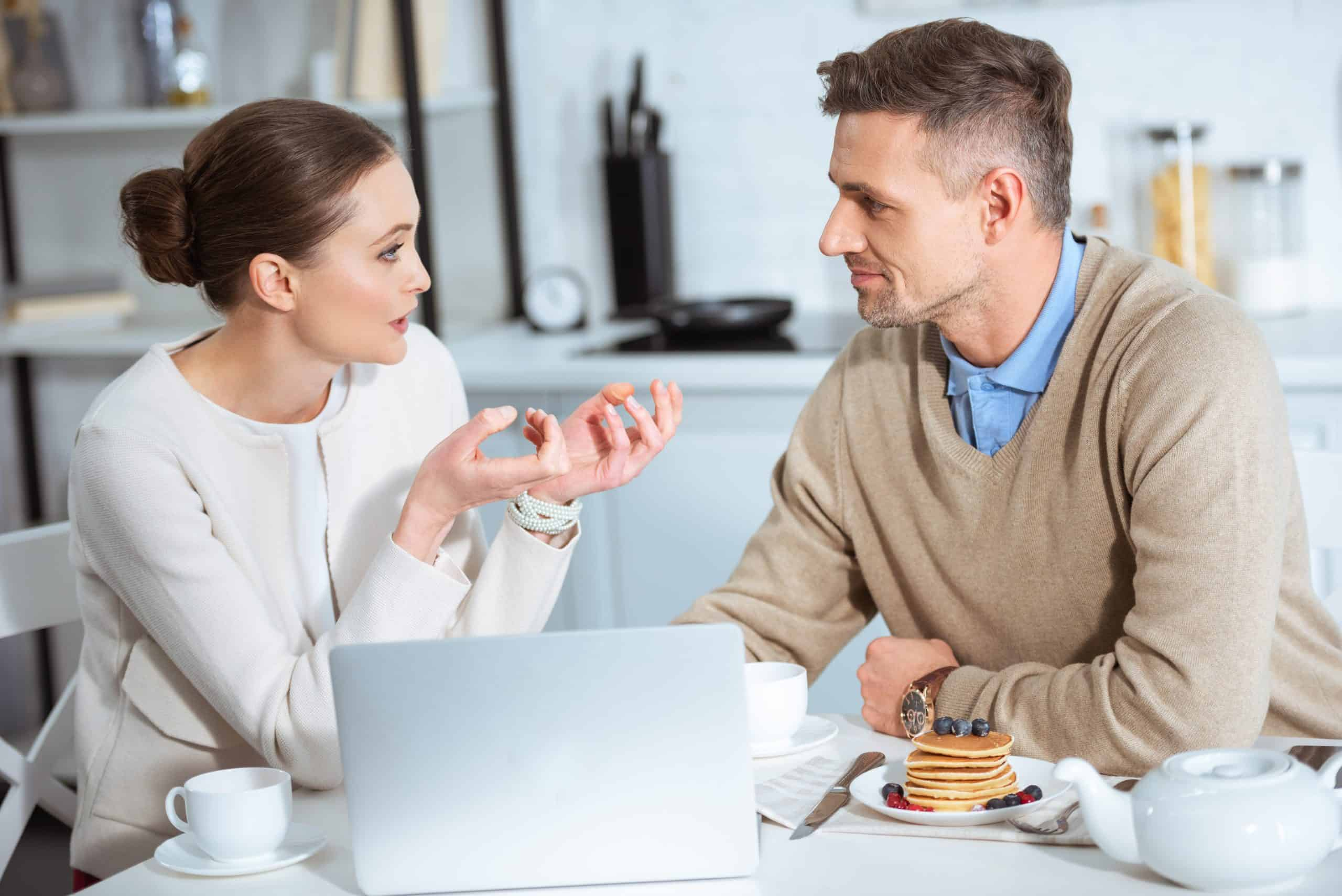 More frugal than spouse - White couple win white kitchen having important discussion with laptop