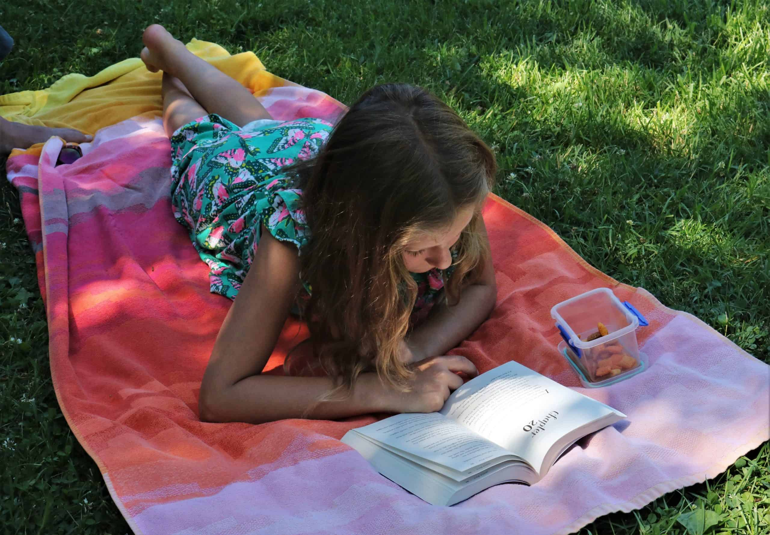 Summer reading programs - girl on striped blanket in grass reading a book