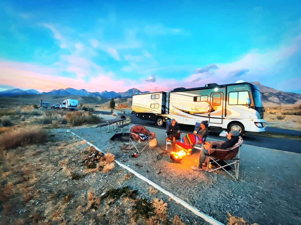 friends outside their rental rv sitting around bonfire with mountain views in the distance