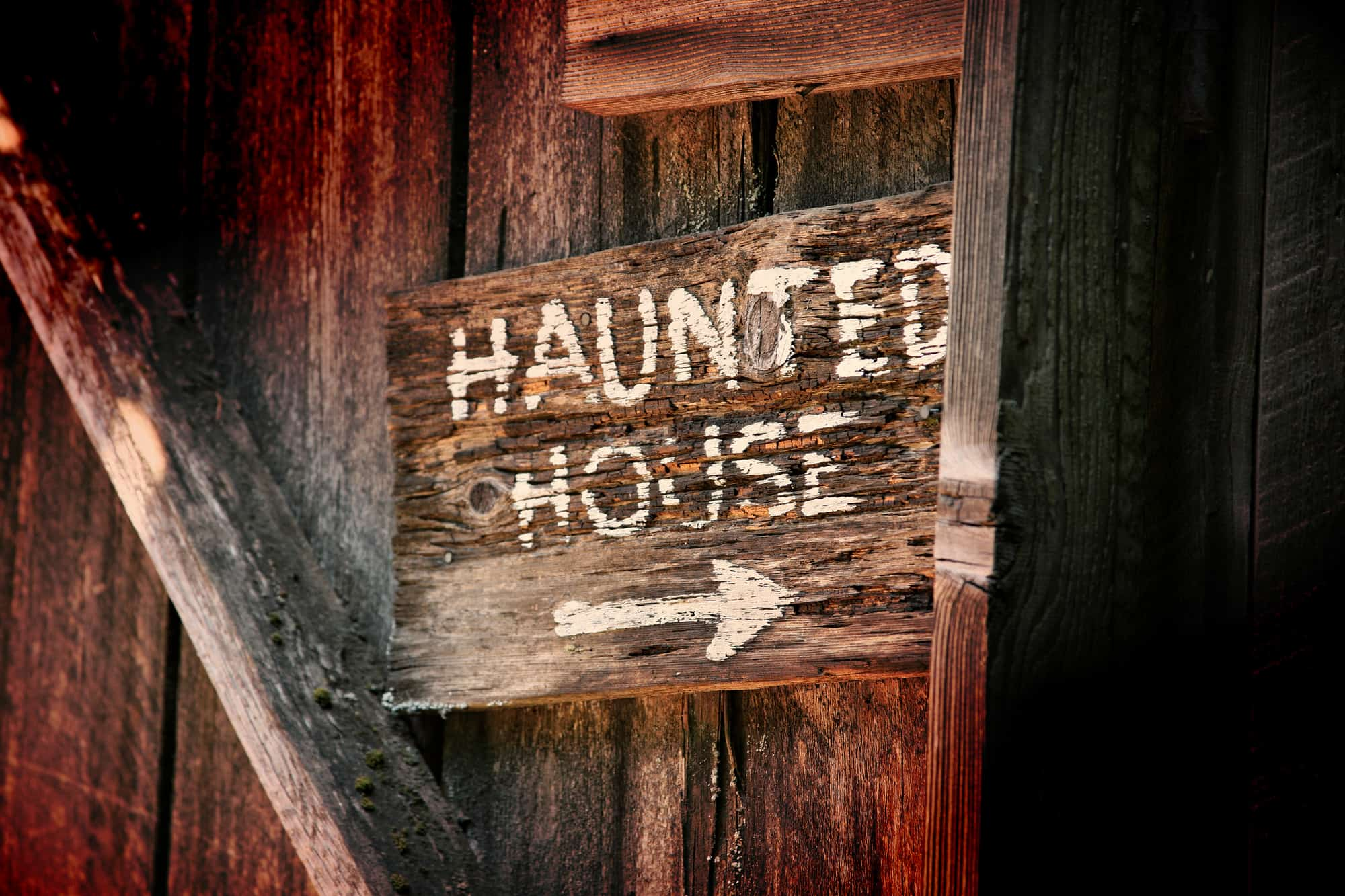 """Wooden """"Haunted House"""" sign with arrow pointing right"""