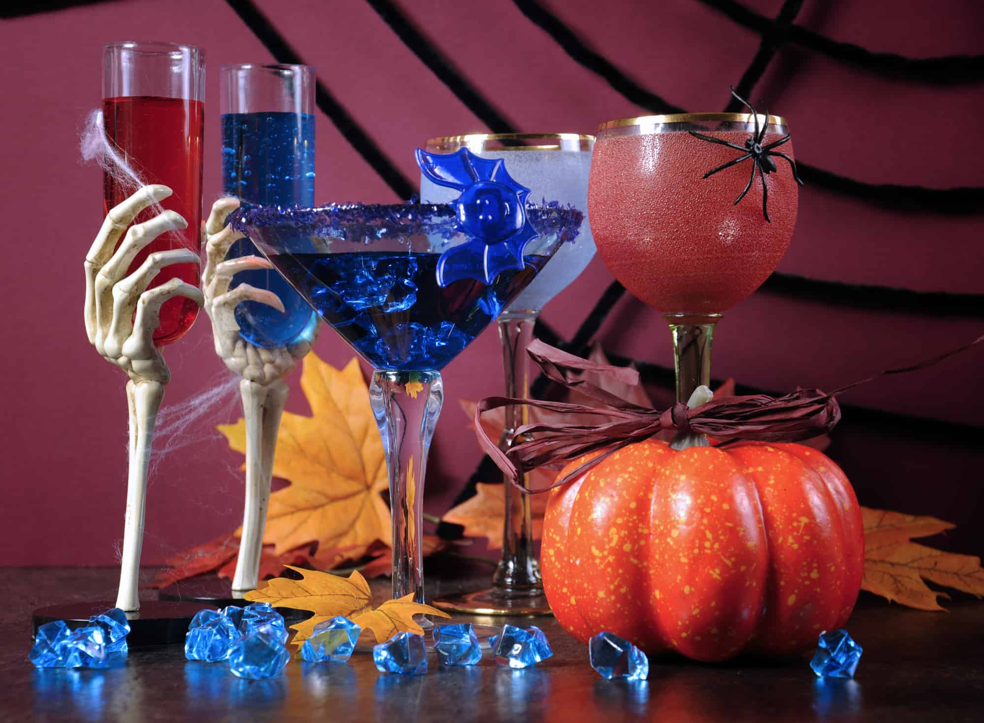 Skeleton hands raising Halloween drinks