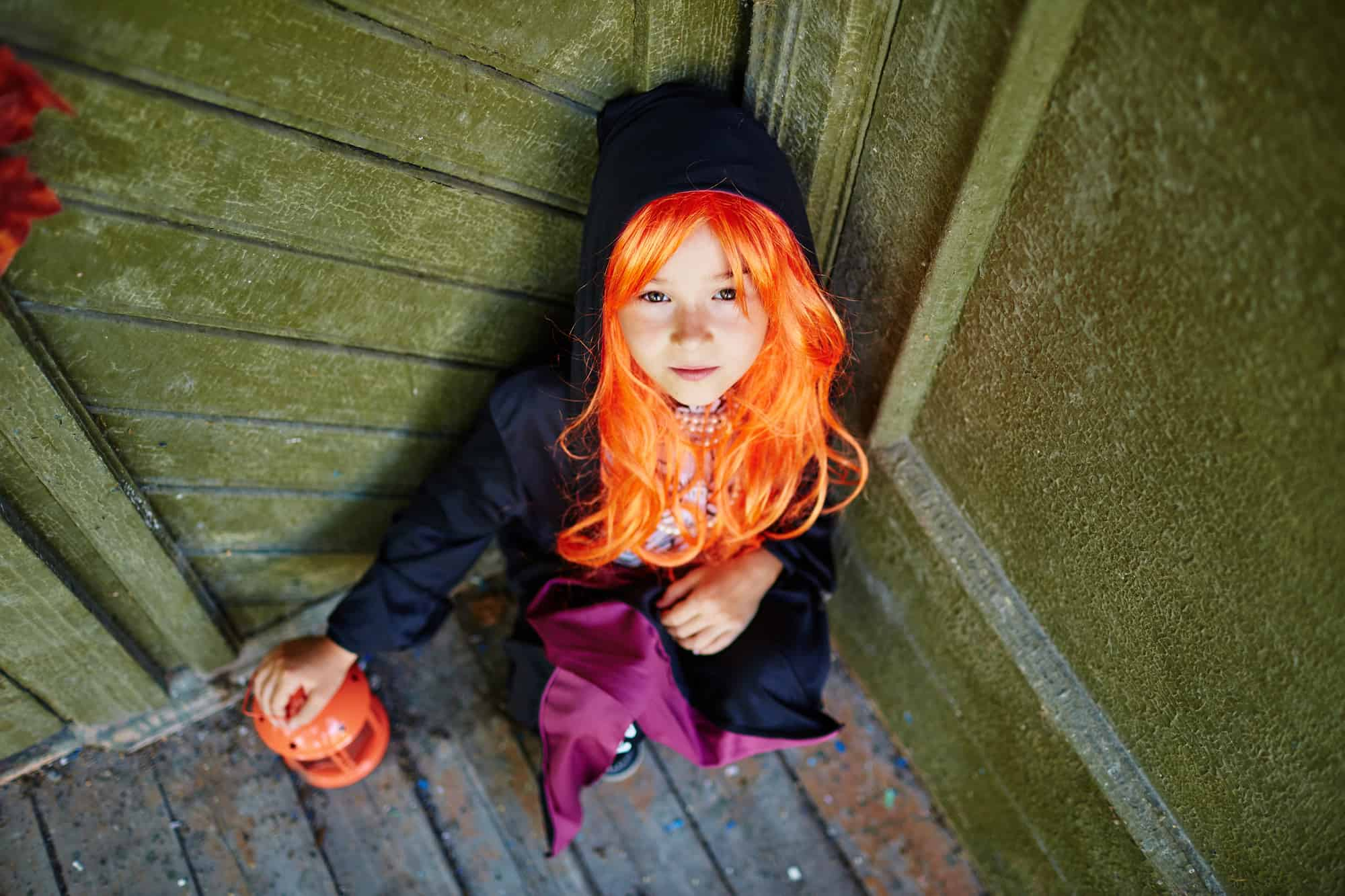 Little girl standing on stairs dressed like a witch