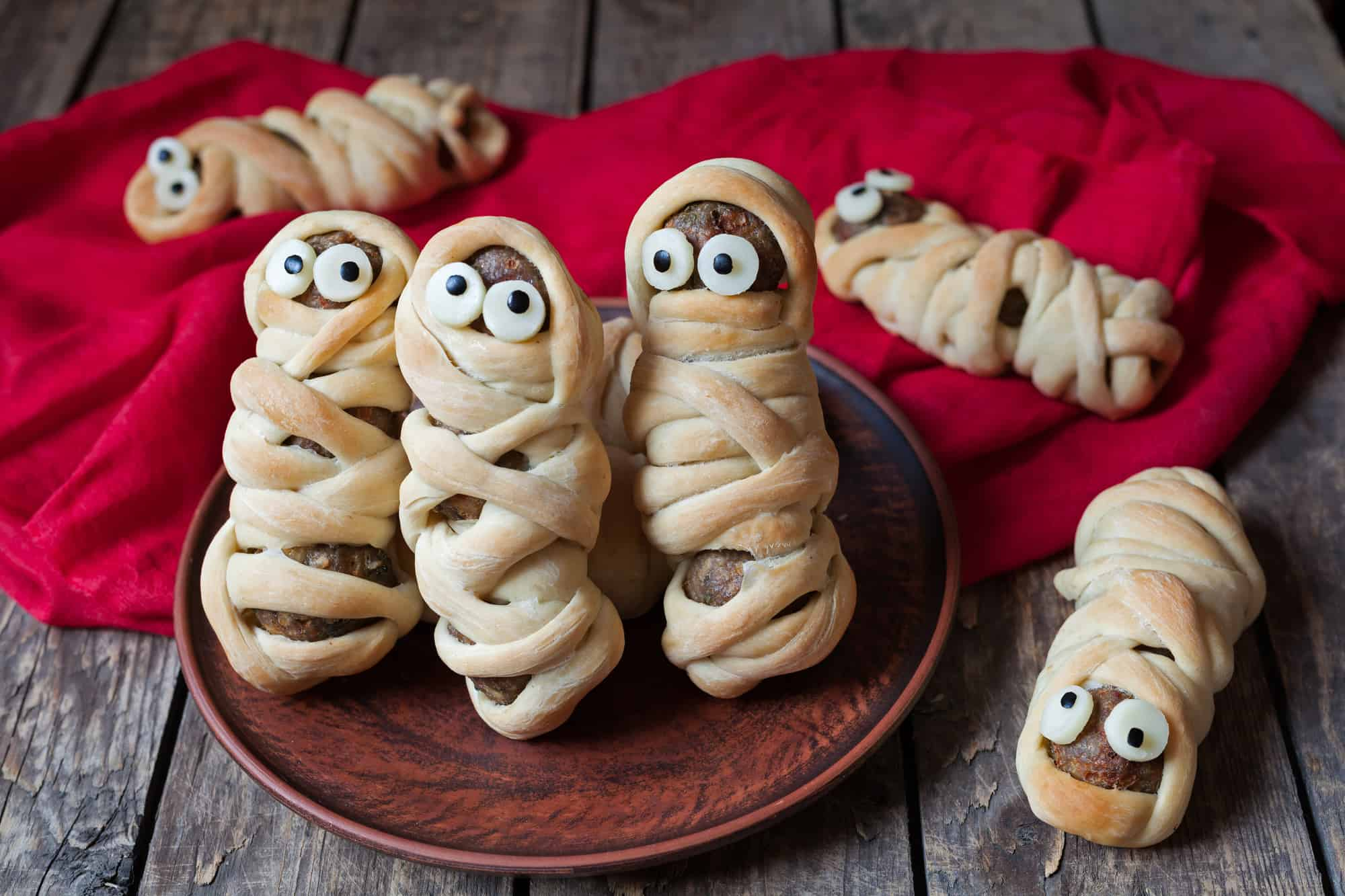 Halloween snack of small hot dogs wrapped like mummies in strips of dough.